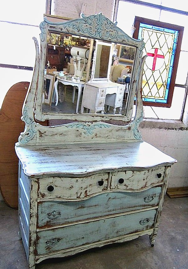 A Two Tone Turquoise Paint Finish Highlights Details On An Antique Wood Dresser