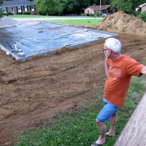 Ray looking at workshop foundation where construction is happening finally