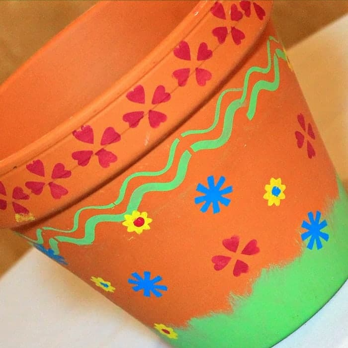 stencil a terra cotta or clay pot with pretty flowers
