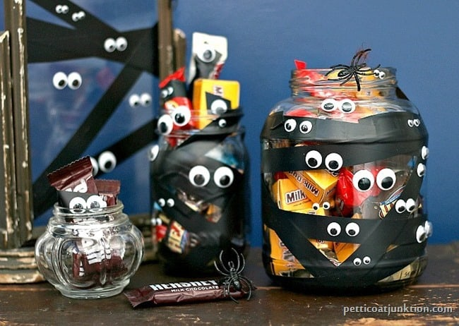Googly eye and black electrical tape decorated Halloween candy jars.