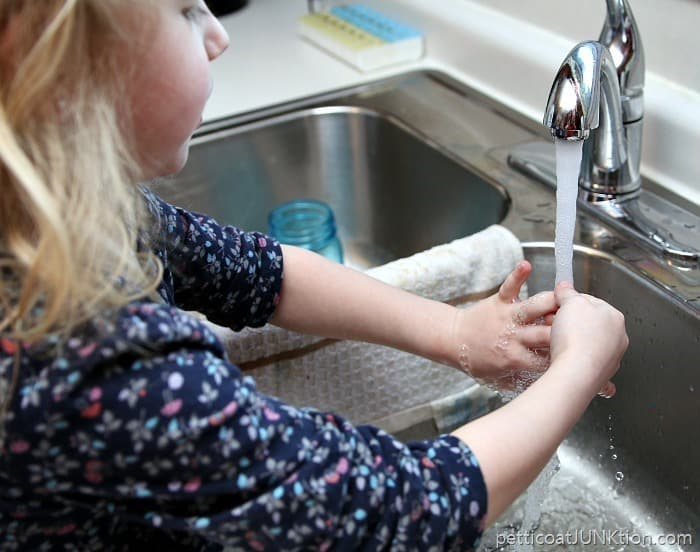 Sofi washing the paint from her hands Petticoat Junktion fingerpainting project