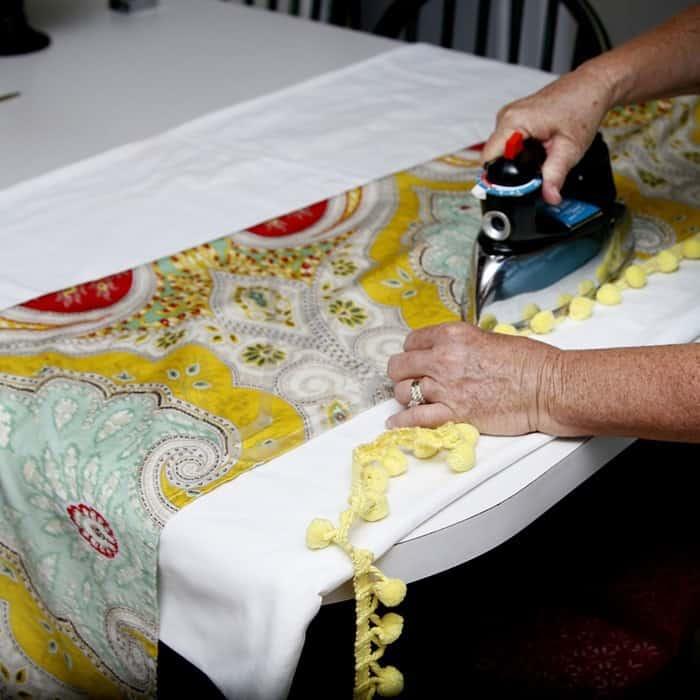 applying pom pom fringe to fabric with adhesive hem tape