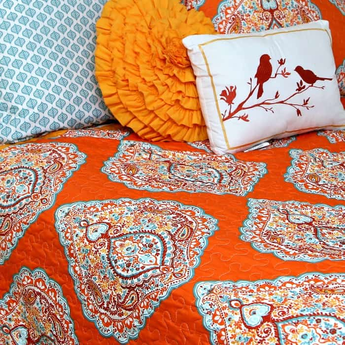 turquoise and orange comforter and decorative pillows