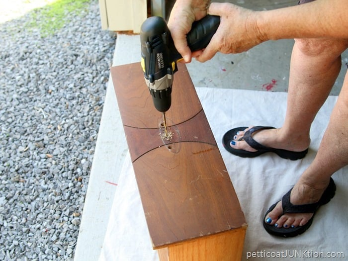 using an electric drill to drill holes for hardware