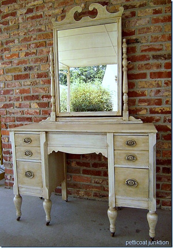Vintage vanity with mirror painted white and aged to look antique.