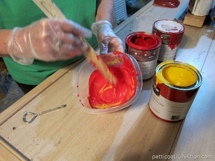 mixing red paint and yellow paint to make coral paint color