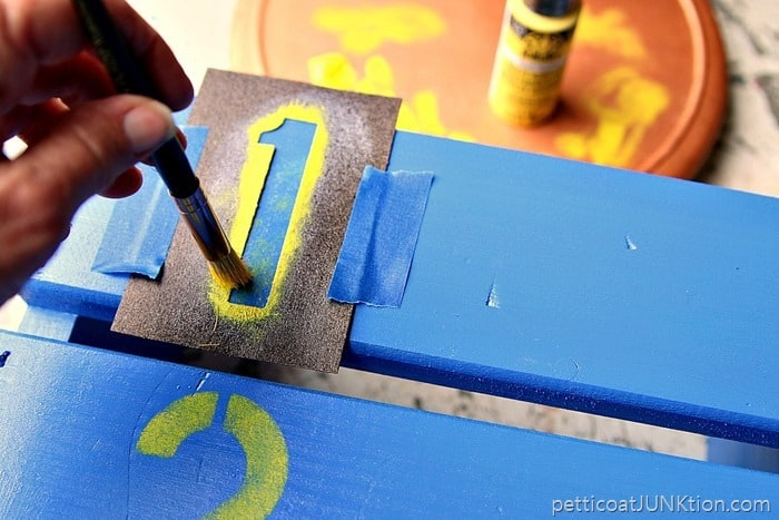 stenciling yellow numbers on a step stool