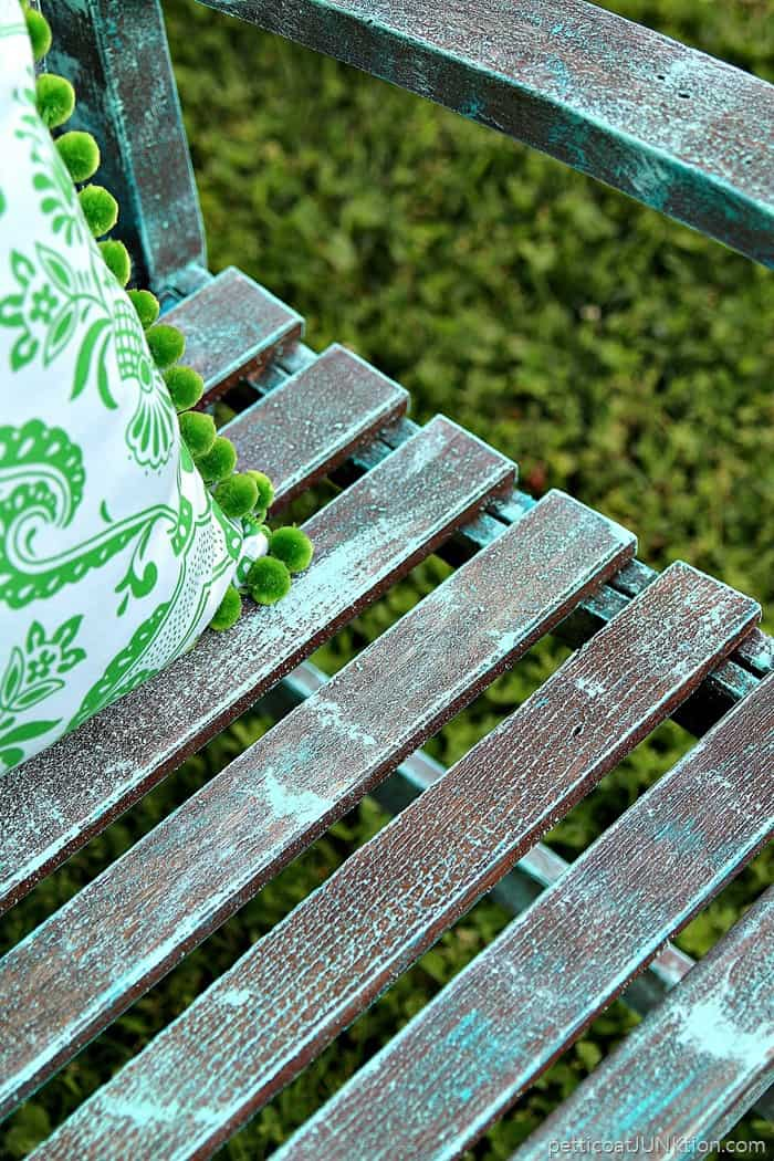 close up look at turquoise paint dry brushed onto the outdoor chair