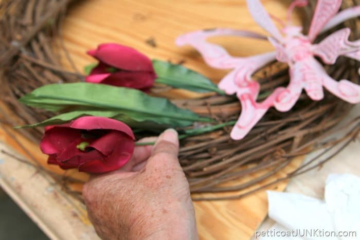 stick the flower stems in the grapevine wreath
