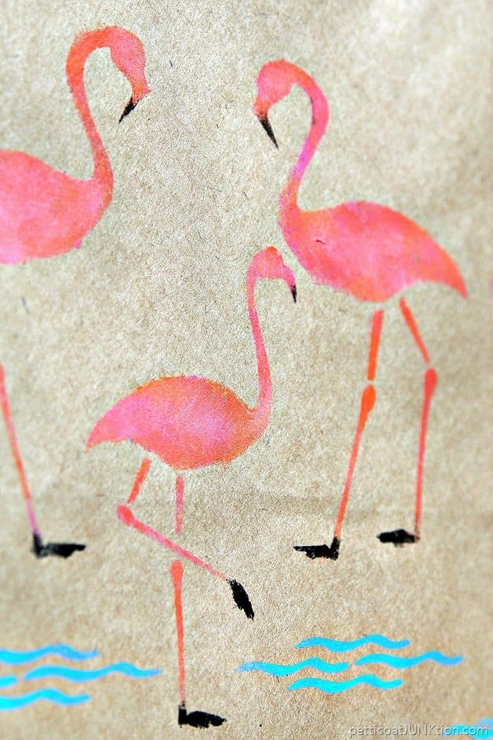 pink flamingos stenciled on a brown kraft paper gift bag