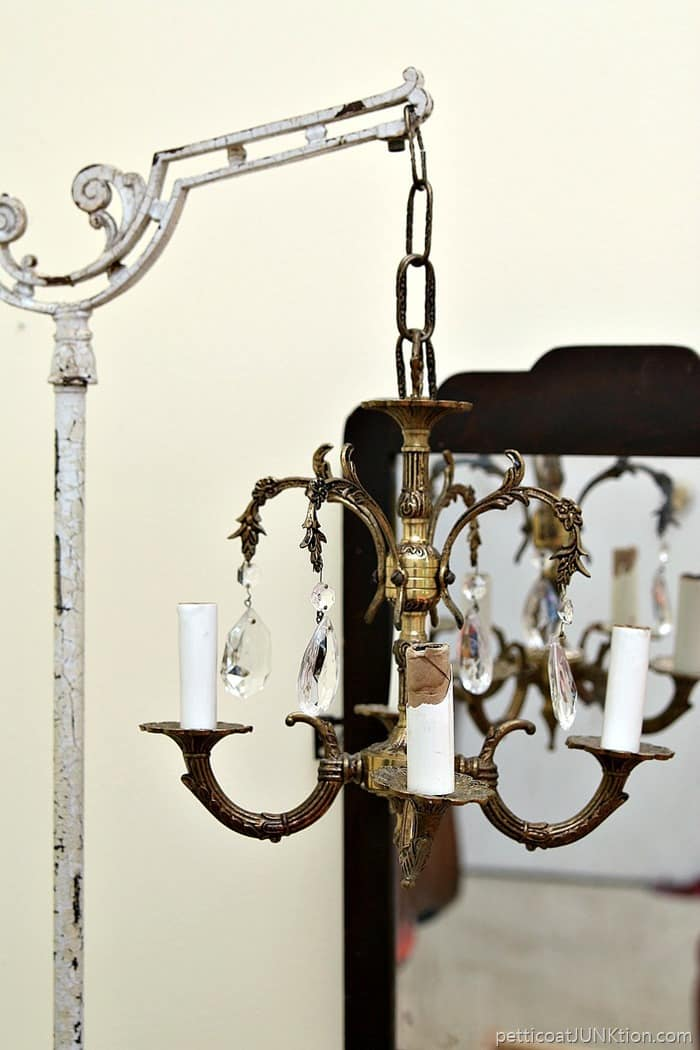 vintage chandelier hanging from chippy white floor lamp stand