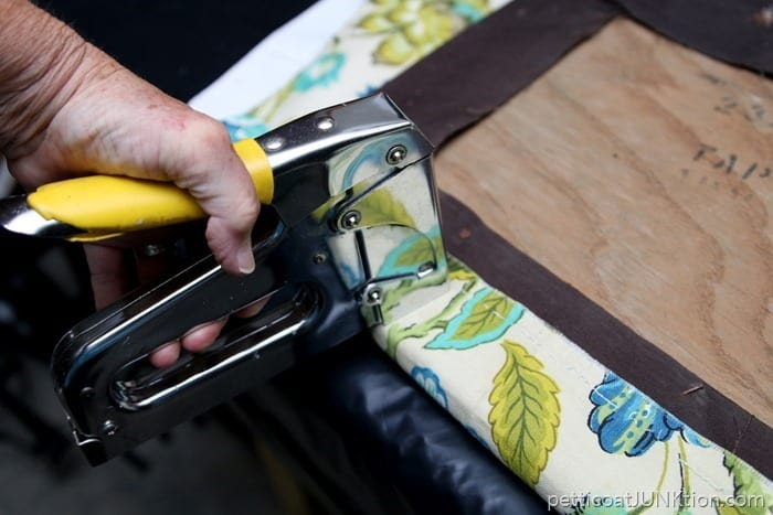 cut fabric to recover chair seat and staple it on