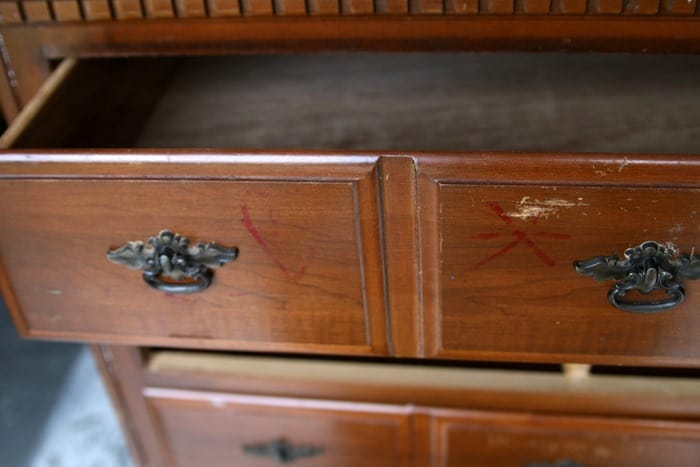 permanent ink and names scratched on drawer fronts
