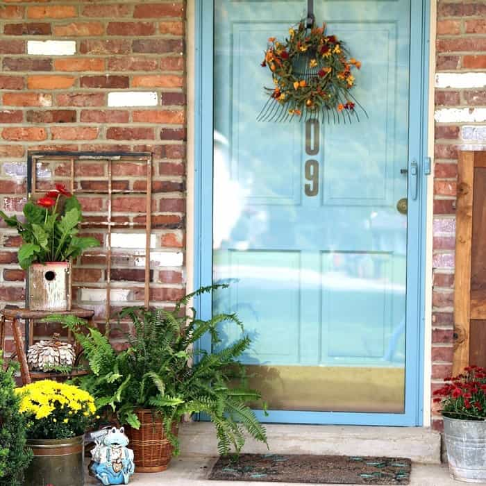 porch decorating using a Wood Birdhouse Flower Container and a rake wreath