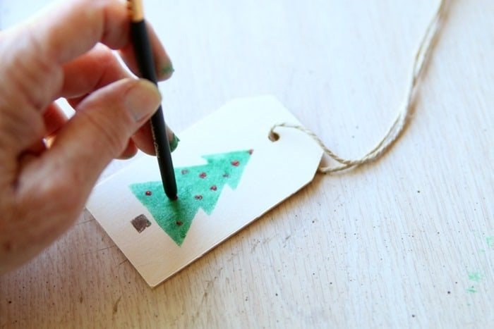 using the tip end of a stencil brush to make ornaments on a tree