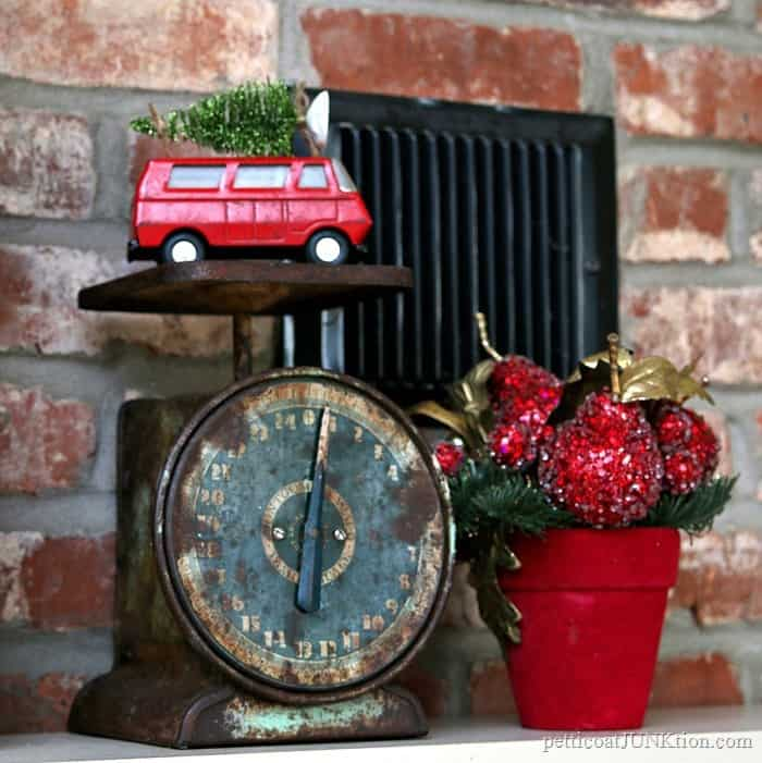 rusty vintage kitchen scale with red van topped with Christmas tree