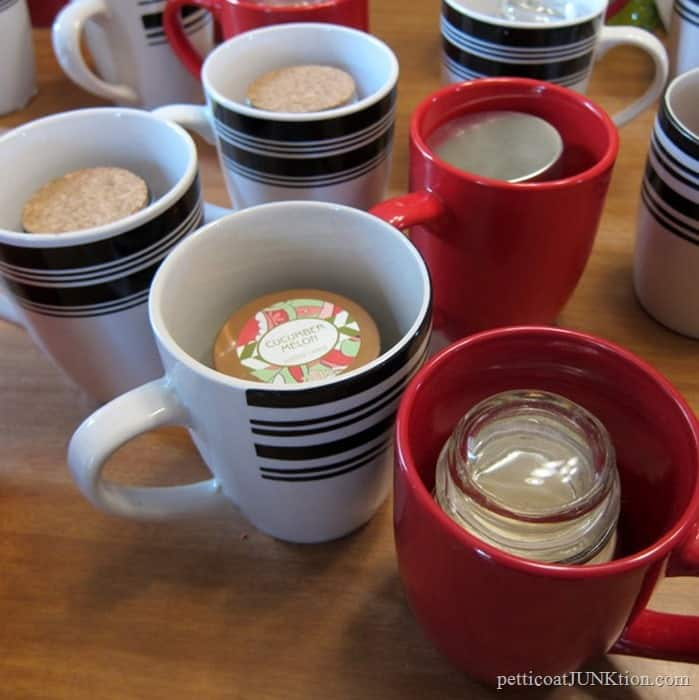 small candles in coffee mugs