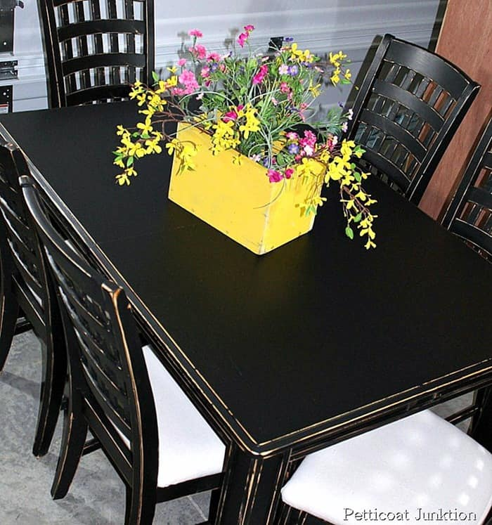 black dining room table and chairs with drop cloth covered seats