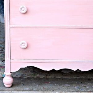 pink chest of drawers with wood knobs