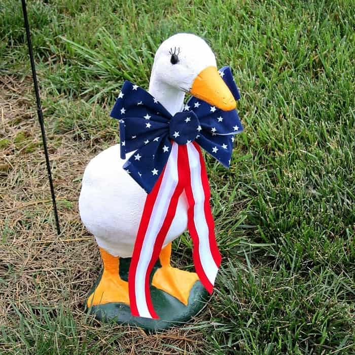 Goose lawn statue with a patriotic box