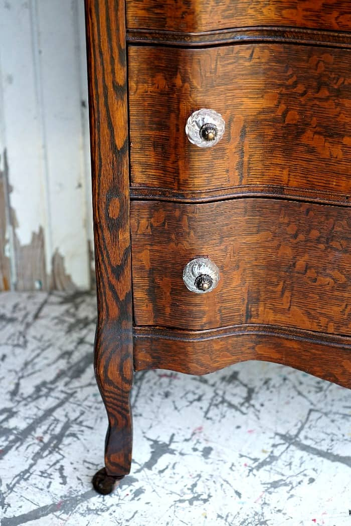 curvy legs and beautiful oak wood of an antique chest of drawers