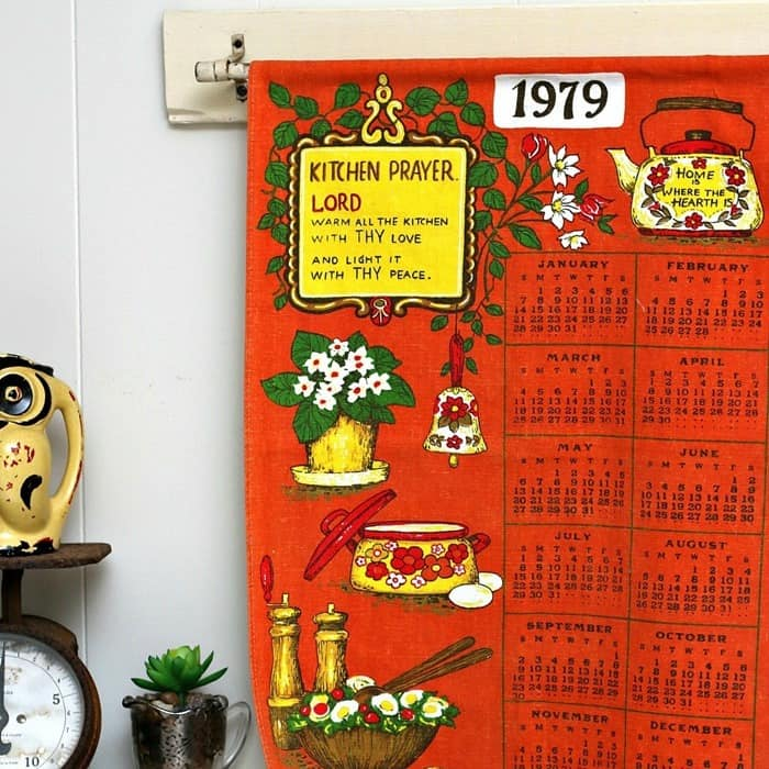 hang a vintage tea towel calender from a curtain rod