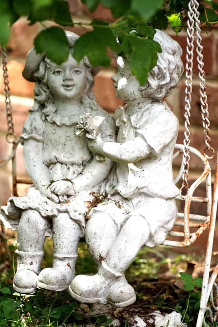 boy and girl on a swing yard statue