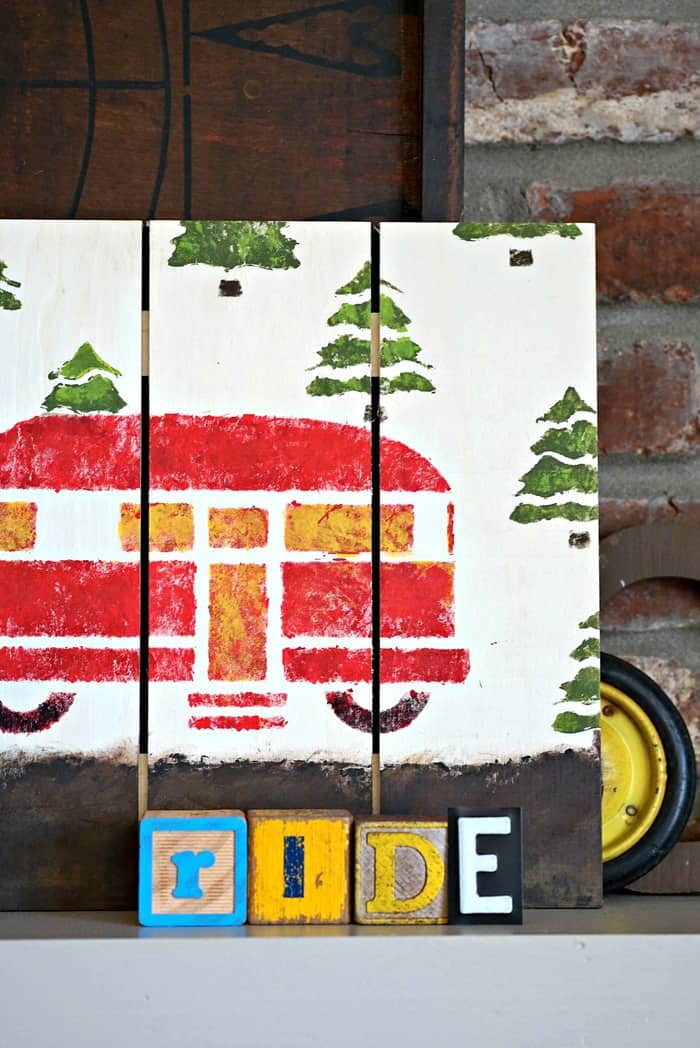 woodland camper wall sign painted in red, green and yellow