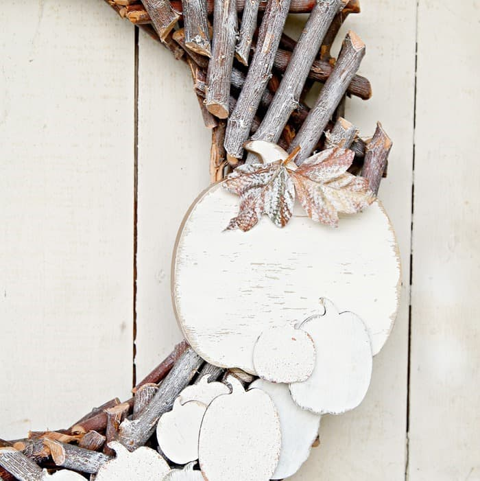 basic wood wreath decorated with pumpkins