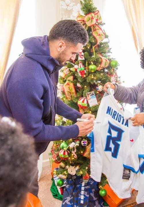 Marcus Mariota Titans Quarterback signing football jersey for Habitat homeowner as part of Homes for the Holidays project
