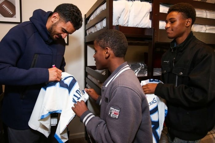 Marcus Mariota signing a jersey for son of Homes for the Holidays recepient