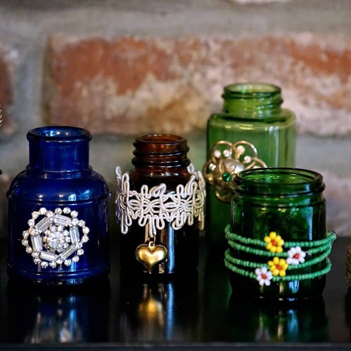small colored bottles decorated with bits and pieces of jewelry