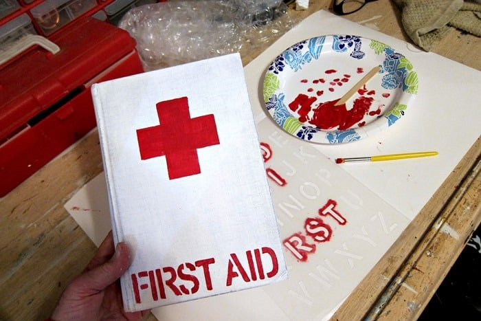 painting an old book to look like a Red Cross First Aid book