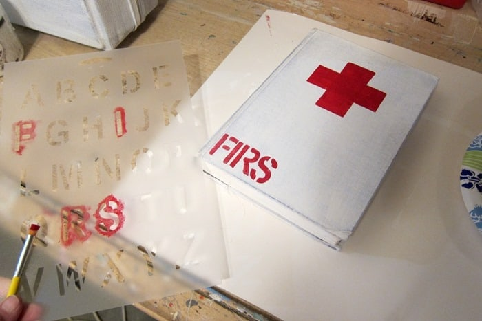 stenciling a painted book to look like an antique red cross first aid book