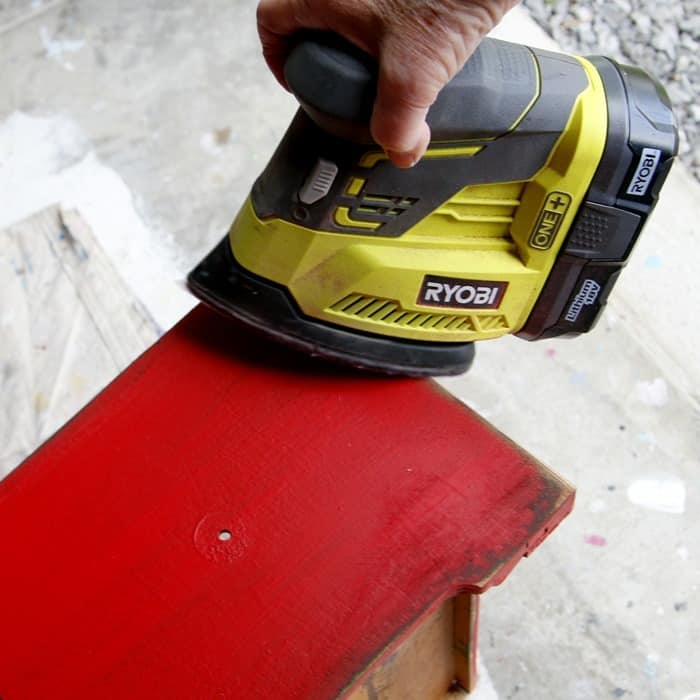 using a battery powered sander to distress painted furniture