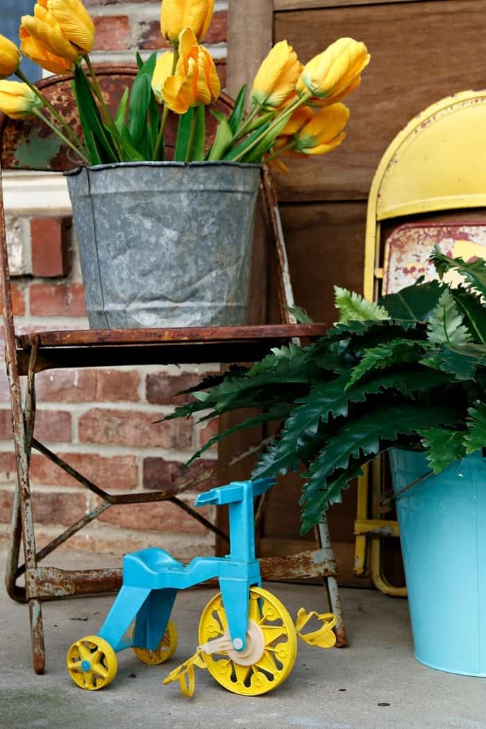 yellow tulips and rusty metal chairs make great Spring porch decorations