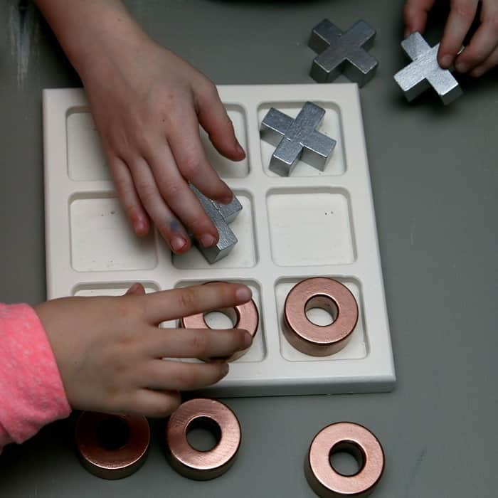 girls playing tic tac toe with metallic painted game pieces