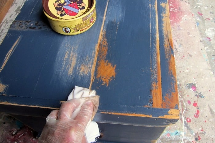 apply a coat of dark wax to distressed paint