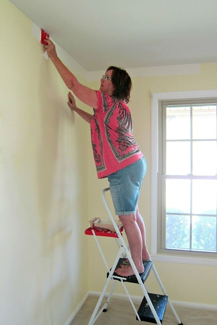cutting in the wall where it meets the ceiling with a paint pad