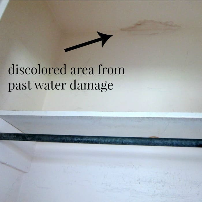 discolored area on wall from past water damage in closet