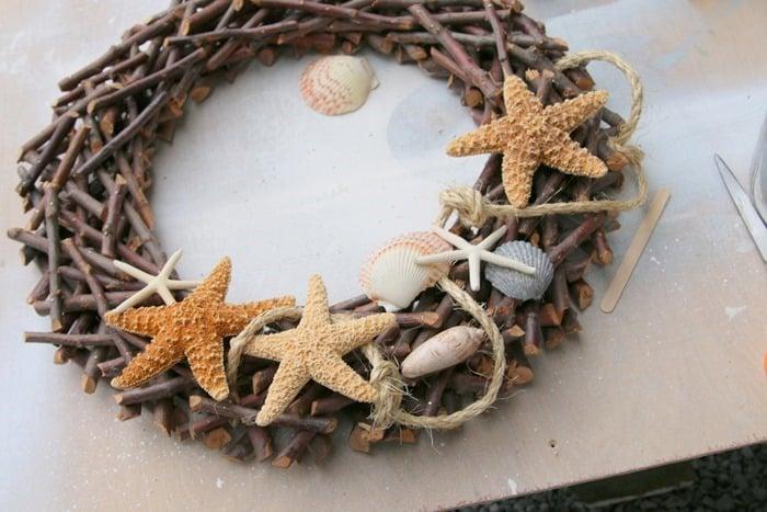 making a beach inspired wreath and adding seashells, sisal rope, and starfish
