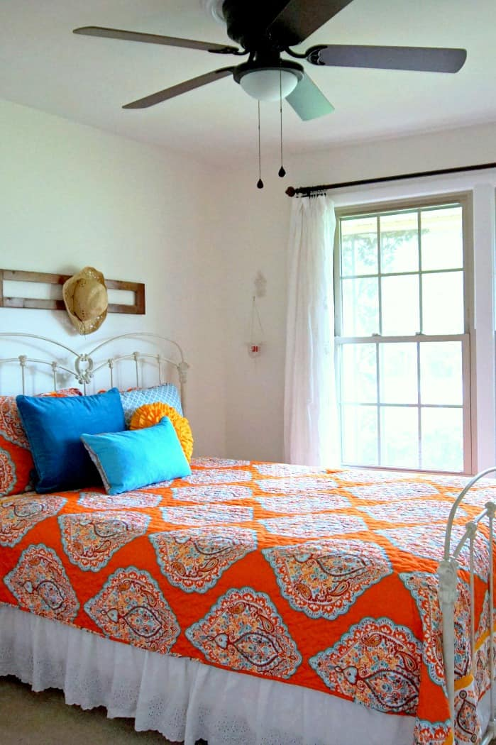 orange and turquoise pops of color in bedroom with white walls