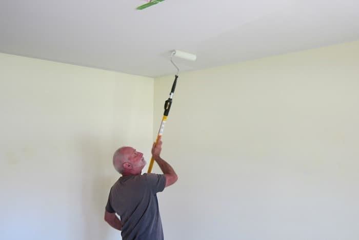 painting the ceiling with a paint pole and roller