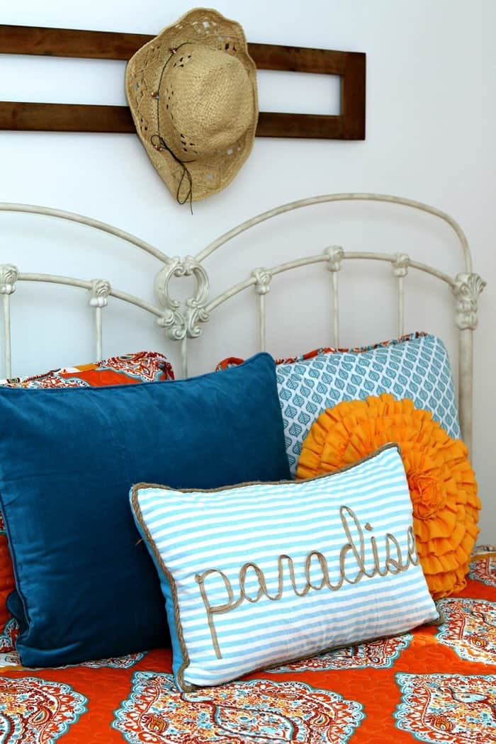 turquoise and orange bedroom makeover with tons of bed pillows