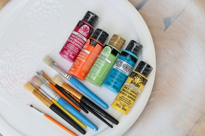 supplies for stencil project include stencil brushes and acrylic paints in bold colors