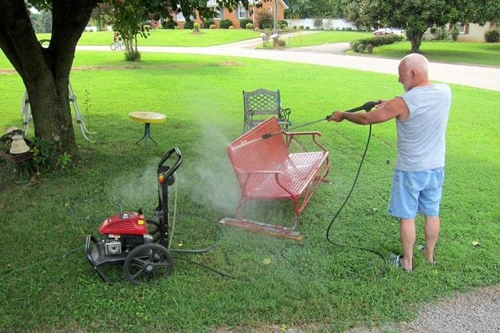 using a pressure washer to wash metal outdoor furniture