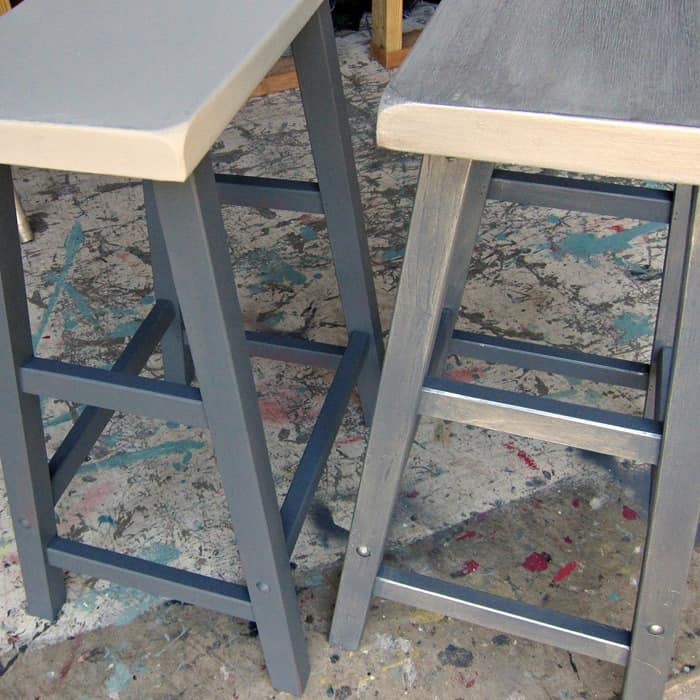 pair of barstools one painted with silver metallic wash and the other with flat gray primer