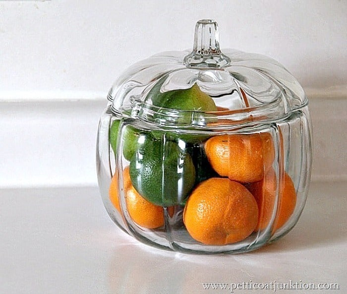 put oranges and limes in a glass pumpkin container for Fall Decor