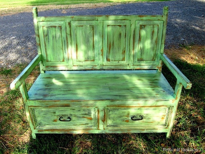 heavily distressed green wood bench with storage