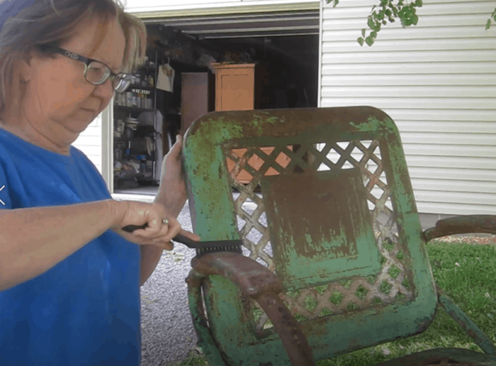 brushing loose paint from rusted metal furniture